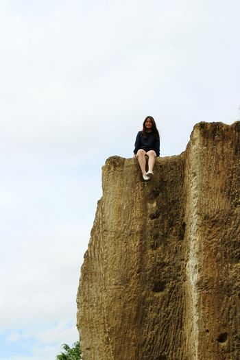 Low angle view of woman sitting on cliff against cloudy sky