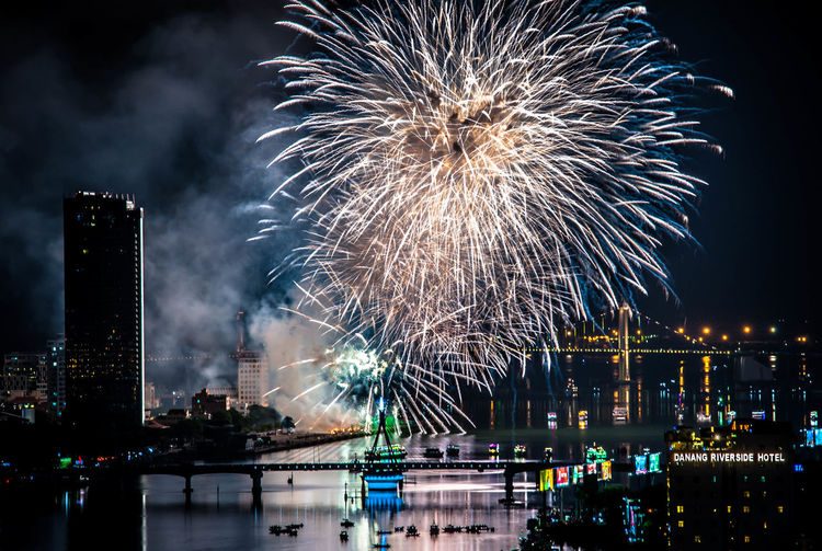 Firework display over river in city at night