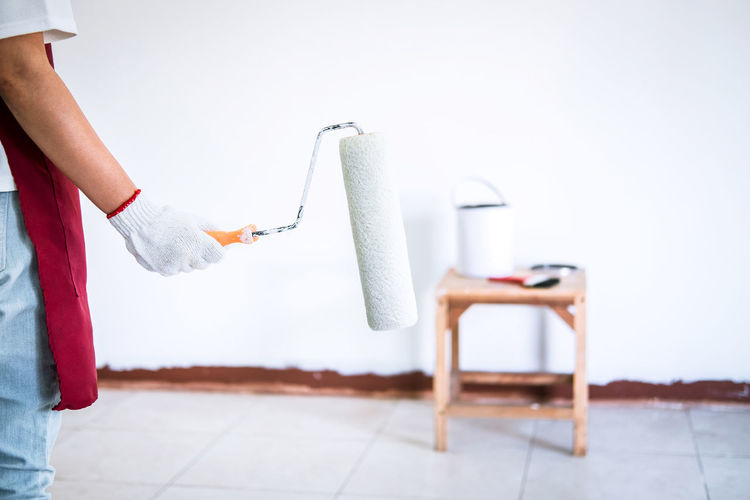 Midsection of painter holding paint roller while painting wall at home