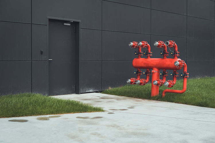 Red pipe against black wall