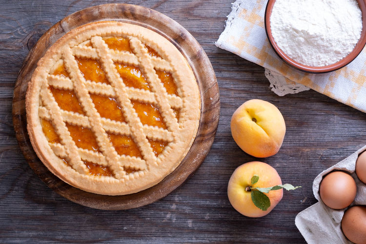 Tart with peach jam on wooden rustic table Tart Apple - Fruit Bowl Container Dairy Product Directly Above Drink Food Food And Drink Freshness Fruit Healthy Eating High Angle View Indoors  No People Peaches Pie Refreshment SLICE Snack Still Life Table Table Knife Wellbeing Wood - Material