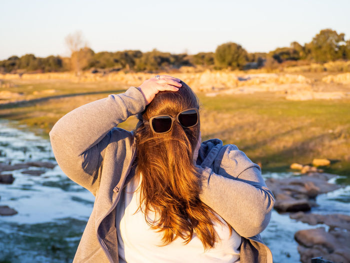 Woman with face covered by hair wearing sunglasses by stream
