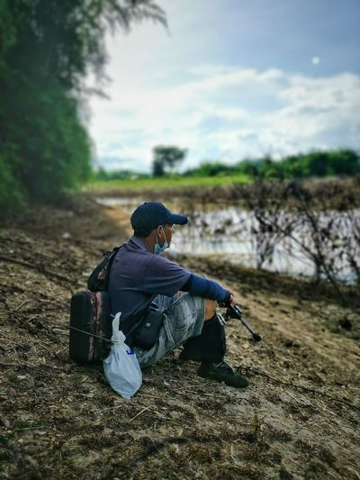 Rear view of man sitting on land against sky