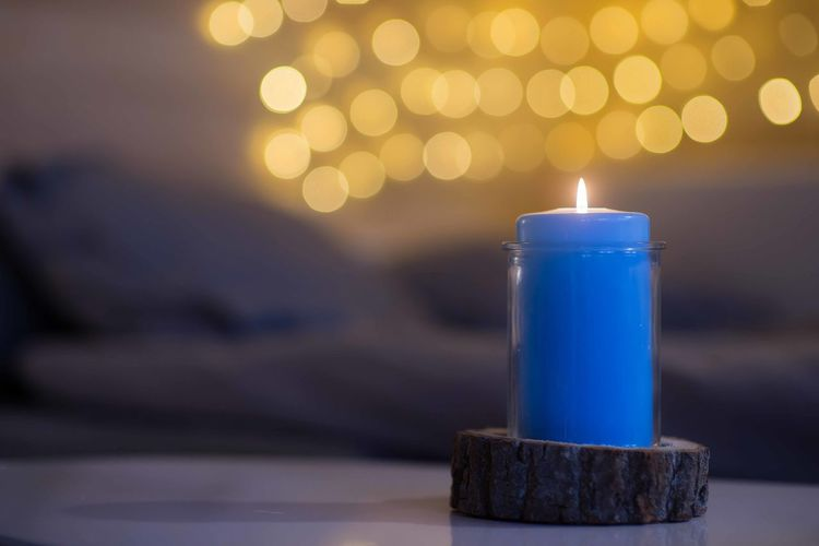 Blue Illuminated Candle Focus On Foreground Burning Flame Close-up Lighting Equipment Table Decoration Night Indoors  Yelow Bokeh Background Celebration Concept Christmas Dinner Party New Year Cabin Life Wooden Mountain Cabin