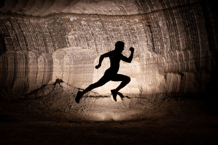 Side View Of Silhouette Man Jumping In Tunnel