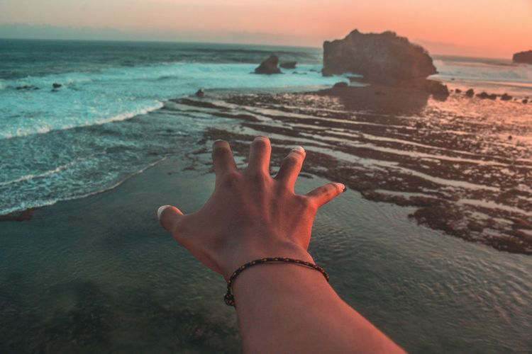 Cropped hand reaching sea during sunset