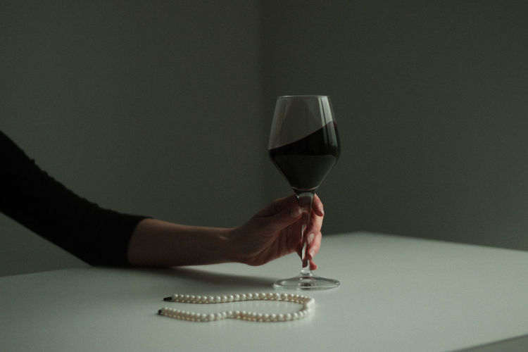 Midsection of woman holding wine glass on table