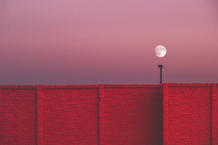 Moon is rising over a red brick wall