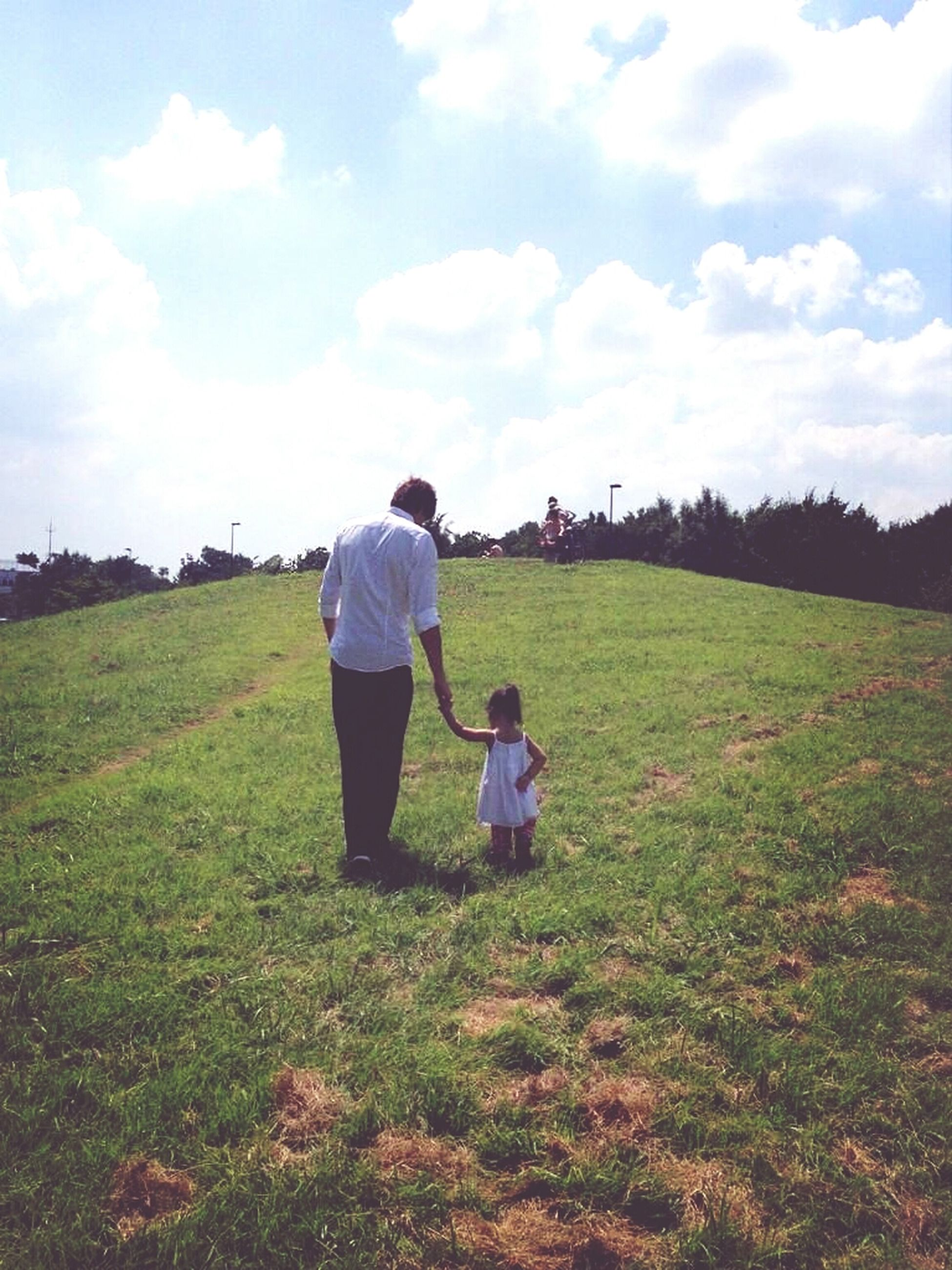 grass, sky, rear view, lifestyles, leisure activity, full length, field, casual clothing, landscape, cloud - sky, men, green color, grassy, nature, tranquil scene, tranquility, person, beauty in nature
