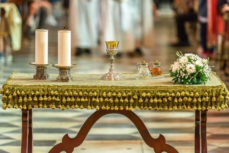 Close-up of wine glass and candles on table at church