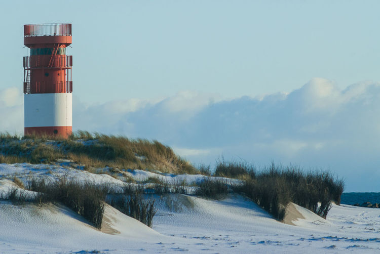 Lighthouse on field against sky during winter