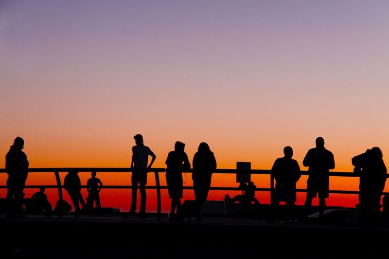 Silhouette people at observation point against sky during sunset