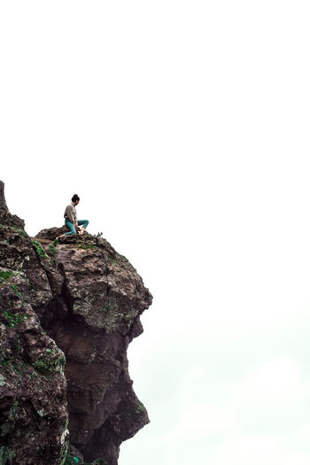 Lonely Rock - Object Cliff Girl White Background Rock Leisure Activity Solid One Person Real People Adventure Lifestyles Activity Sky Rock Formation Nature Copy Space Men Full Length Day Beauty In Nature Side View Outdoors At The Edge Of Formation