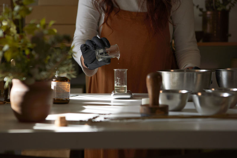 Midsection of woman standing by coffee cup on table