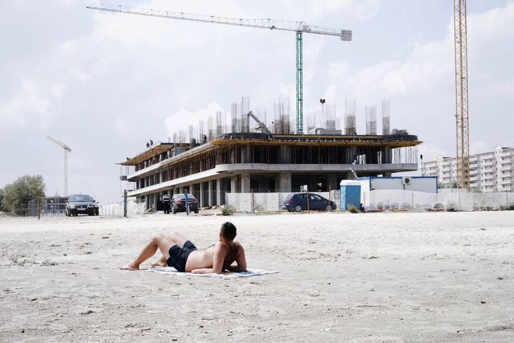 Shirtless man relaxing at beach against incomplete building in city