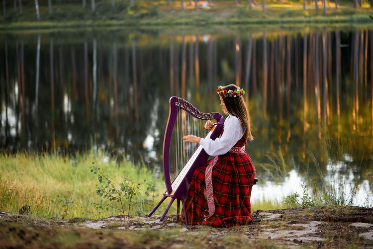 Woman Playing Instrument By Lake
