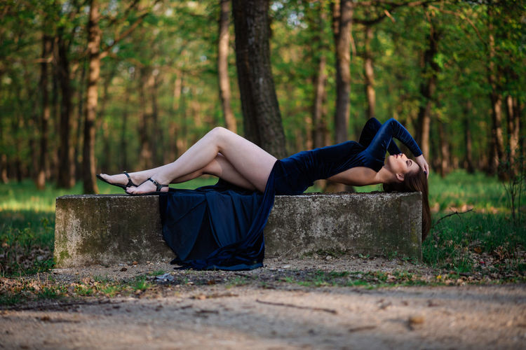 Woman lying on land in forest