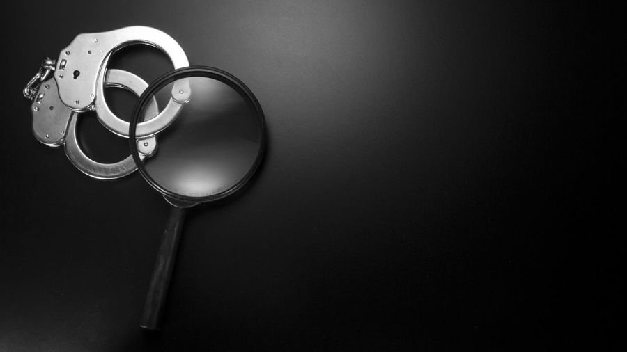 Close Up Of Magnifying Glass With Handcuffs