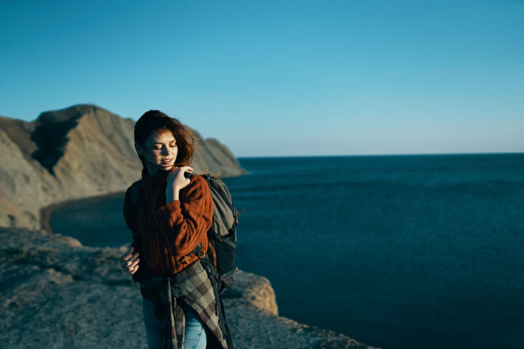 Young woman standing by sea against sky
