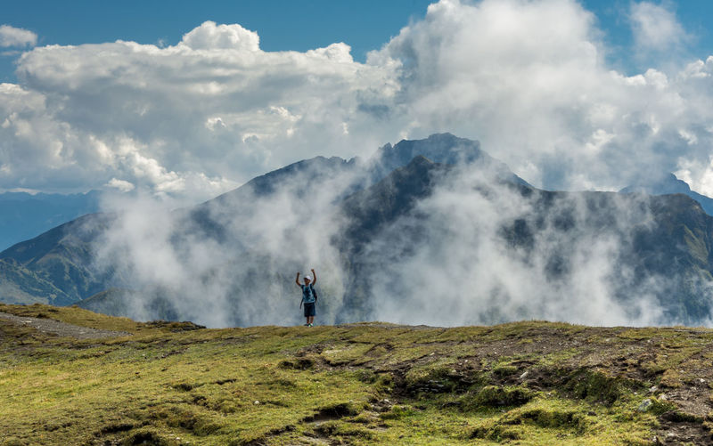 Excited Man Standing On Mountain Peak Against Sky
