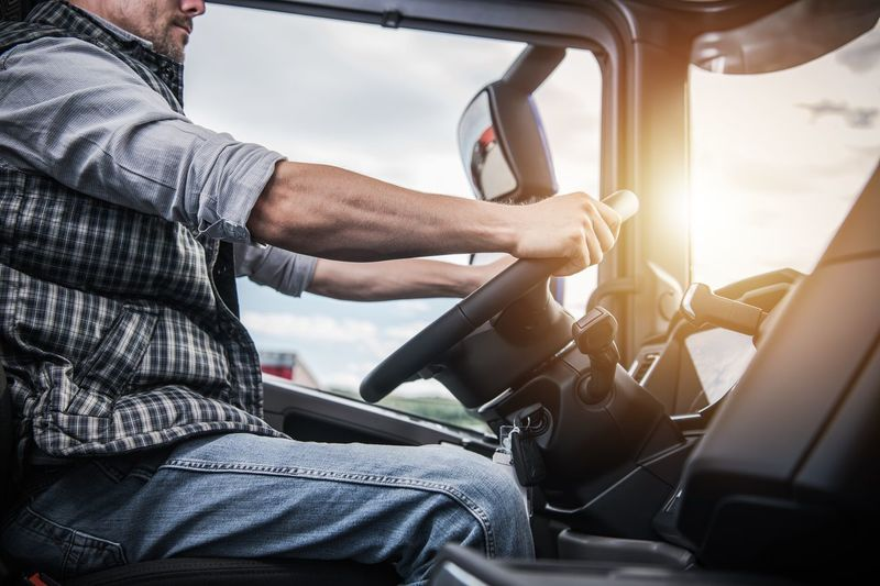Midsection of men driving truck
