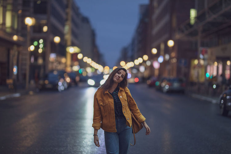 Portrait of young woman standing on road in city at night