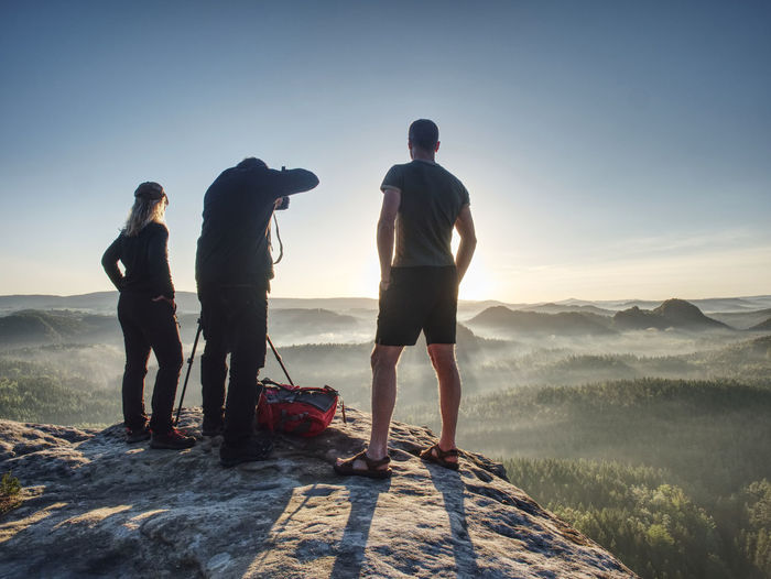 Three friends photographers discuss and taking photo from sticking out rock above misty pandscape