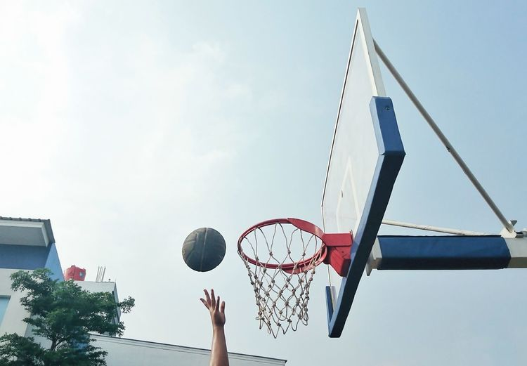 Low angle view of person playing basketball against sky