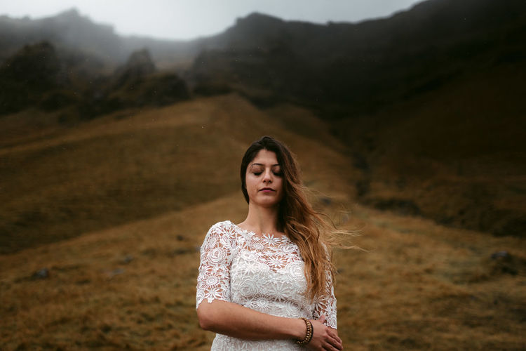 Woman standing on mountain by road against sky