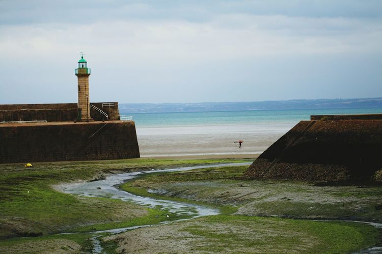Lighthouse Beach Sea Building Exterior Water Built Structure Architecture Horizon Over Water Sand No People Sky Outdoors Grass Travel Destinations Day Sand Dune Nature Mammal Bilic Bretage Tide Lonely One Person Premium Collection EyeEm Premium Collection Breathing Space
