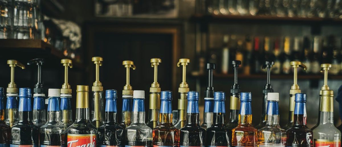 Fruit syrup bottles lined up on a coffee shop Coffee Shop Bottle Alcohol Large Group Of Objects Container No People Food And Drink Side By Side Drink Focus On Foreground In A Row Close-up Glass - Material Indoors  Bar - Drink Establishment Still Life Business