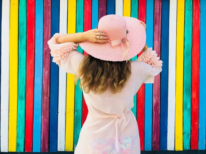 Back of woman wearing pink dress and pink hat standing in front of a colorful vertical striped wall Architecture Building Hairstyle Young Adult In A Row Vibrant Color Vertical Lines Striped Striped Wall Stripes Bright Colors Bright Colors Colorful Wood - Material Wooden Wall Standing Beachwear Fashionable Style Fashion Hat Dress Rear View Back Woman Summer