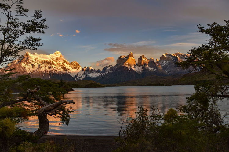 Scenic view of lake against sky and mountains during sunrise at torres del paine national park