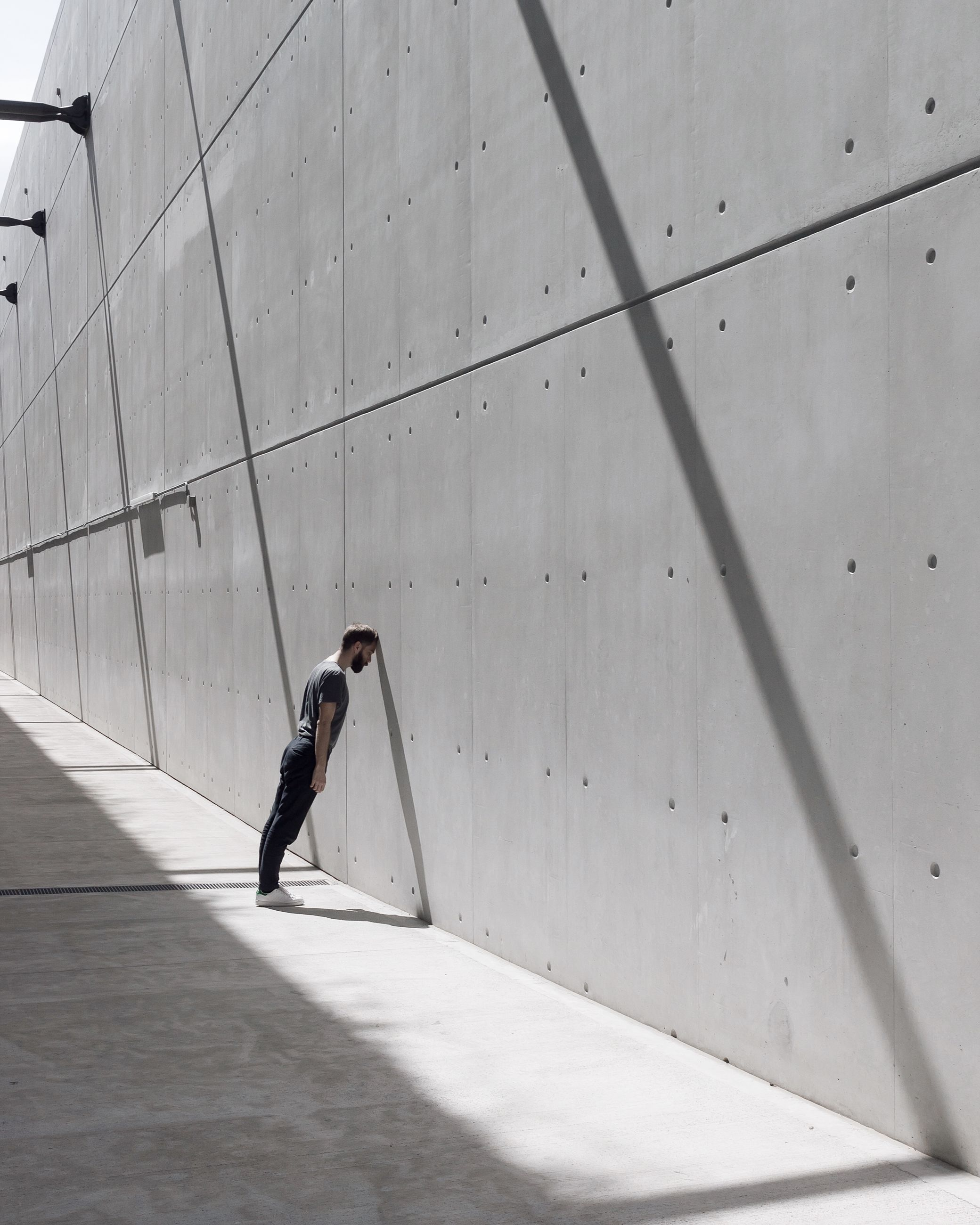 one person, architecture, full length, built structure, real people, wall - building feature, men, walking, leisure activity, day, shadow, side view, indoors, lifestyles, building, casual clothing, sunlight, nature, flooring, concrete