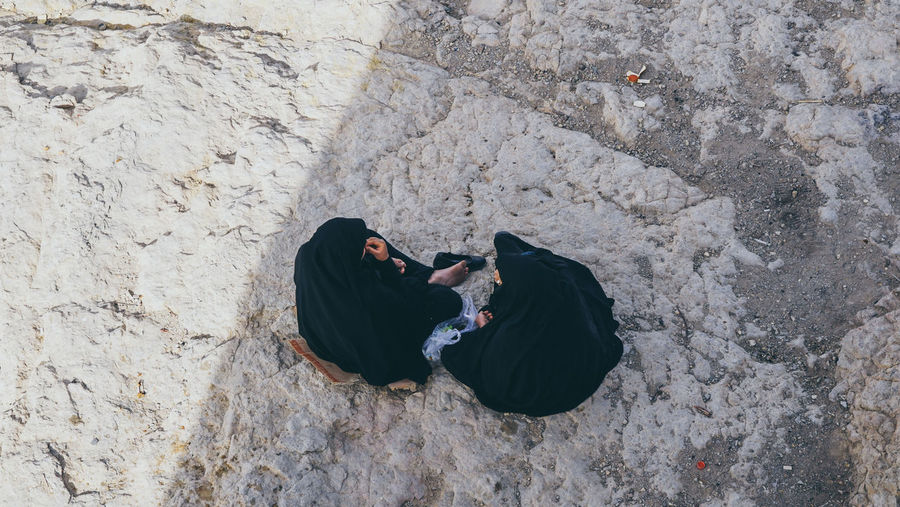 High angle view of women wearing hijab while sitting on field