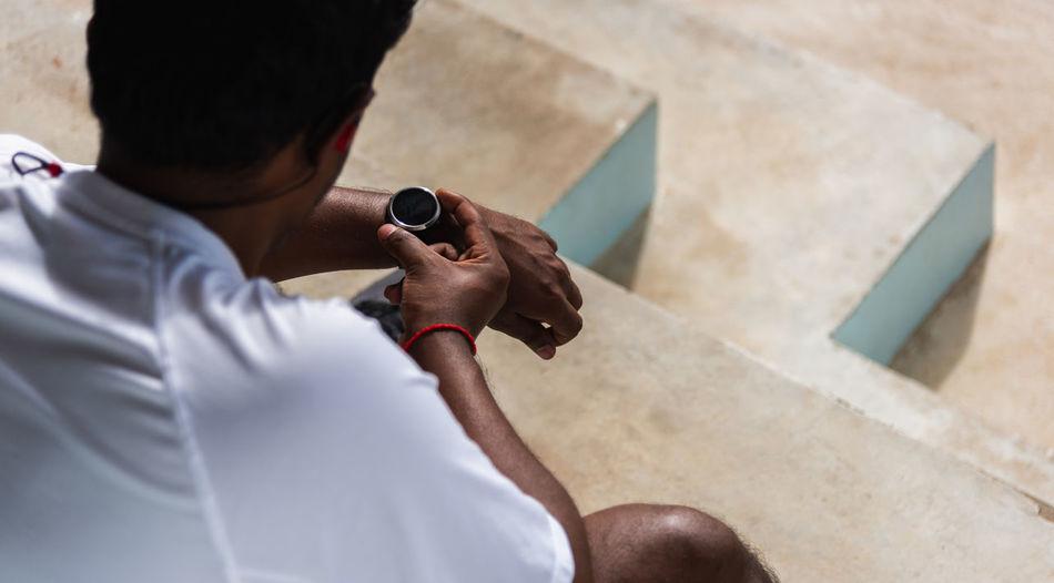Sport runner black man wear modern time smart watch he sitting resting before training running