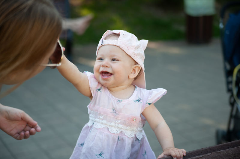 Cute baby girl touching mother while standing outdoors