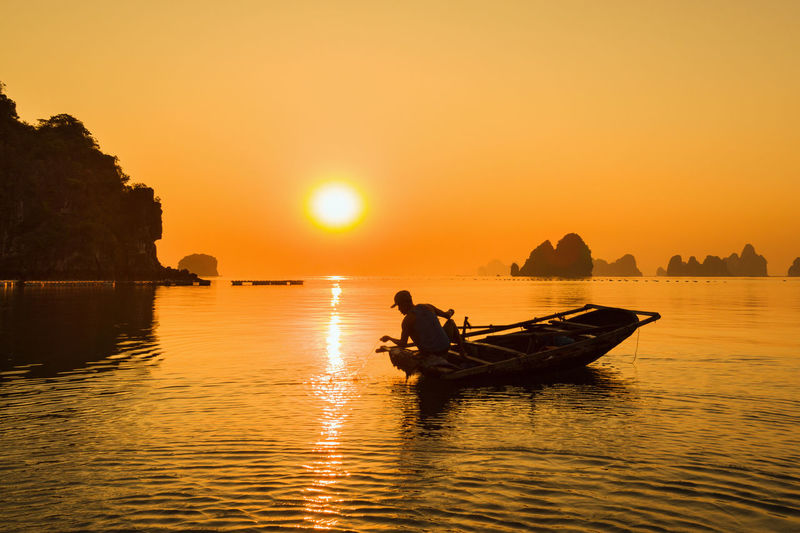 Silhouette man sitting on boat in sea against sky during sunset