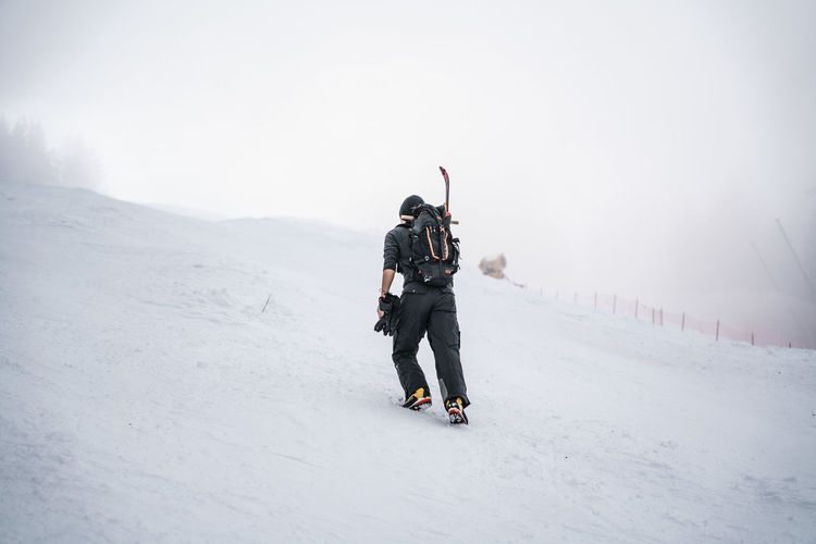 Rear view of man on snow covered landscape against sky during winter