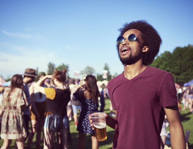 Young African man drinking beer at the festival Music Festival Beer Drink Man Alcohol Hold Outdoors Traditional Festival Celebrate African American African Boho Music Party Summer Festival Entertainment Copy Space Carefree Freedom Adult Young Adult Sunglasses Fashion Fashionable Vacations Youth Culture Traveling Carnival Live Event Shout Scream Popular Music Concert Sunlight Sunny Mouth Open