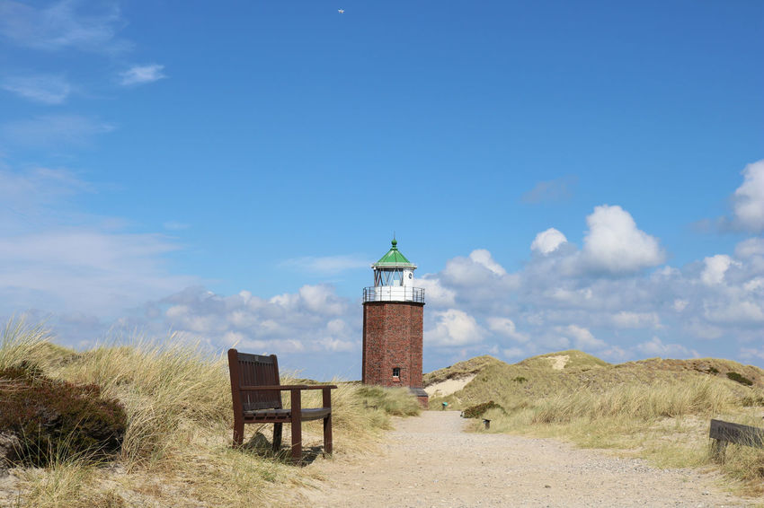 Landscape of Rotes Kliff lighthouse, on the island of Sylt, Germany, located on a cliffside north of the village of Kampen. Bench Dunes Hiking Kampen Path Rotes Kliff, Sylt Architecture Blue Built Structure Day Dune Germany Iconic Island Landscape Lighthouse Nature No People North Sea Outdoors Red Cliff Scenics Sky Sylt Way
