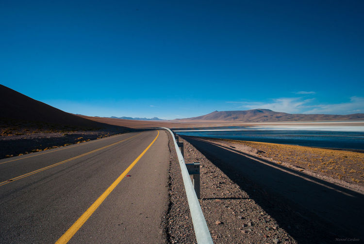 Empty Road By Lake Against Clear Blue Sky On Sunny Day