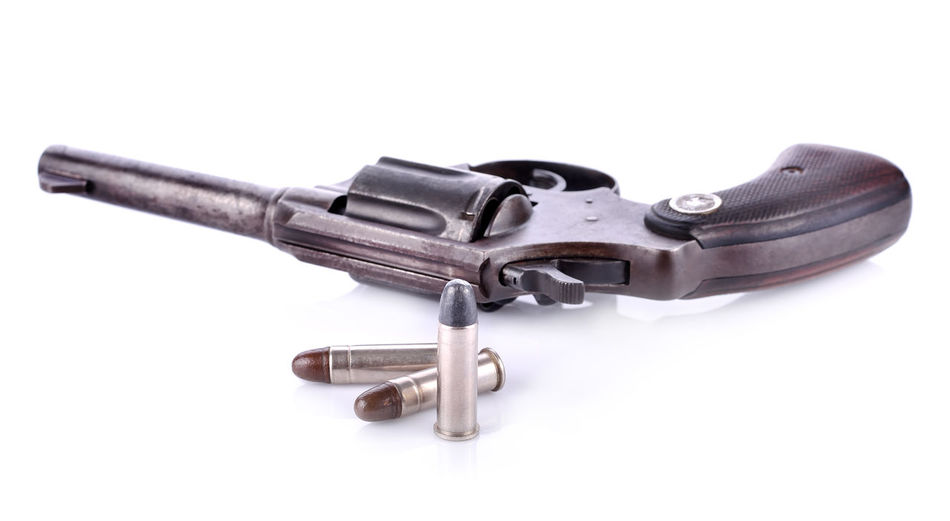 Close-up of revolver over white background