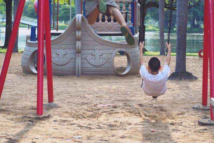 Children playing on swing in playground