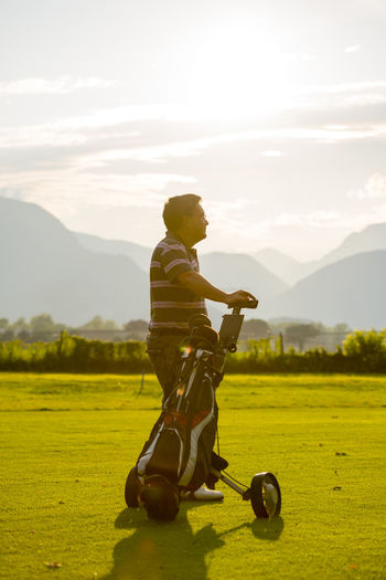 Man standing with golf bag against sky during sunset