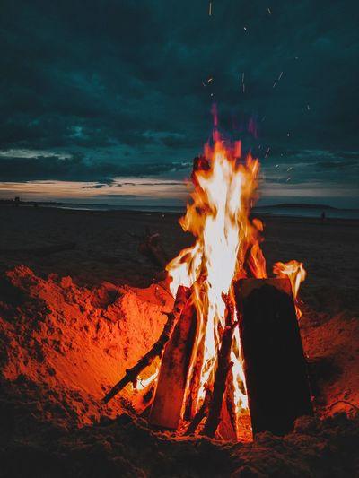 Bonfire on log against sky