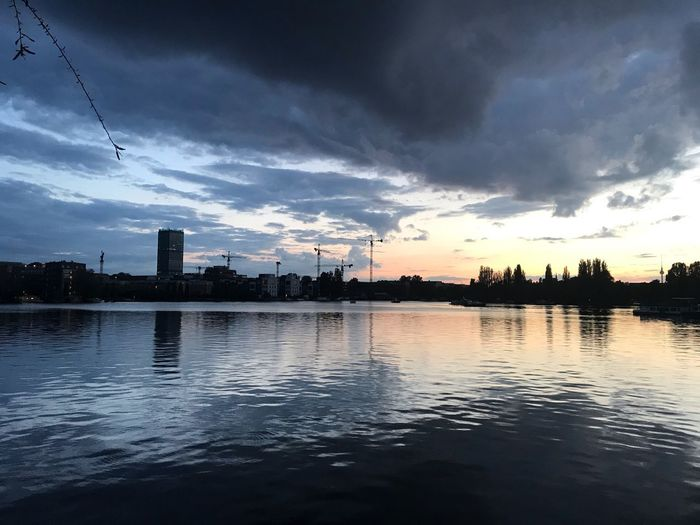 Silhouette buildings by lake against sky at sunset