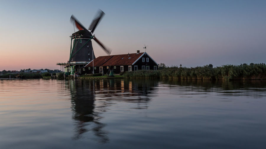 Traditional windmill by lake against sky
