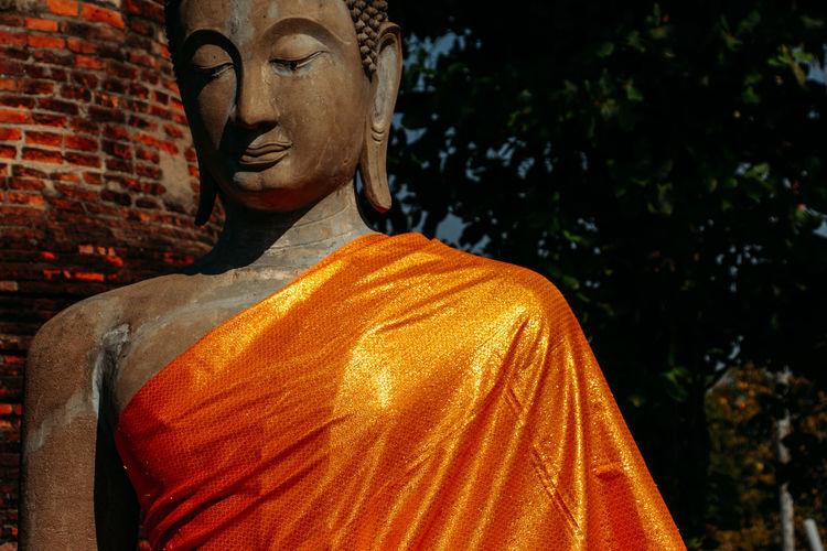 Statue of buddha against orange wall