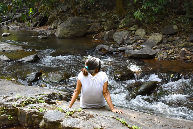Rear view of woman sitting on rock looking at waterfall